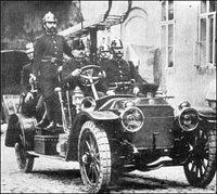 """Dopravní hasičský automobil r.v.: 1910 Praga """"Alfa"""" vyjíždí k zásahu z improvizované hasičské zbrojn"""