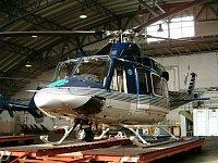Bell 412HP na transportním podvalníku v ruzyňském hangáru PČR LS. Pod trupem je pátrací reflektor SX
