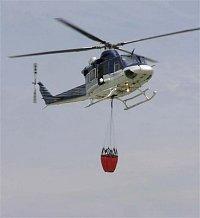 Palubní operátor vykloněný z pootevřených dveří nákladové kabiny navádí vrtulník na shoz vody Foto P