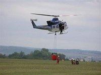 Policejní Bell-412EP, OK-BYP. Palubní operátor, stojící na pravé přistávací ližině, navádí piloty k