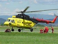 Mi-171 s otevřenou zadní nákladovou rampou nakládá hasičskou skupinu. Na boku vrtulníku jsou patrné