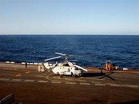 vrtulník na palubě, před ním stojí tým lodních hasičů