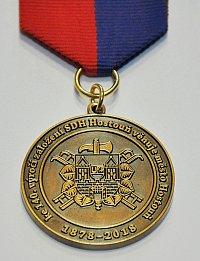 Detail pamětní medaile s vlastní grafikou – znak hasičského sboru doplňuje upomínkový text.