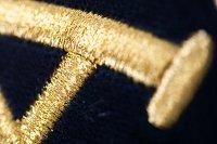 Aby bylo dosaženo efektního výsledku, je třeba i u ruční výšivky písma dodržet tradiční postupy. Detail výšivky zlatého nápisu na slavnostním praporu.